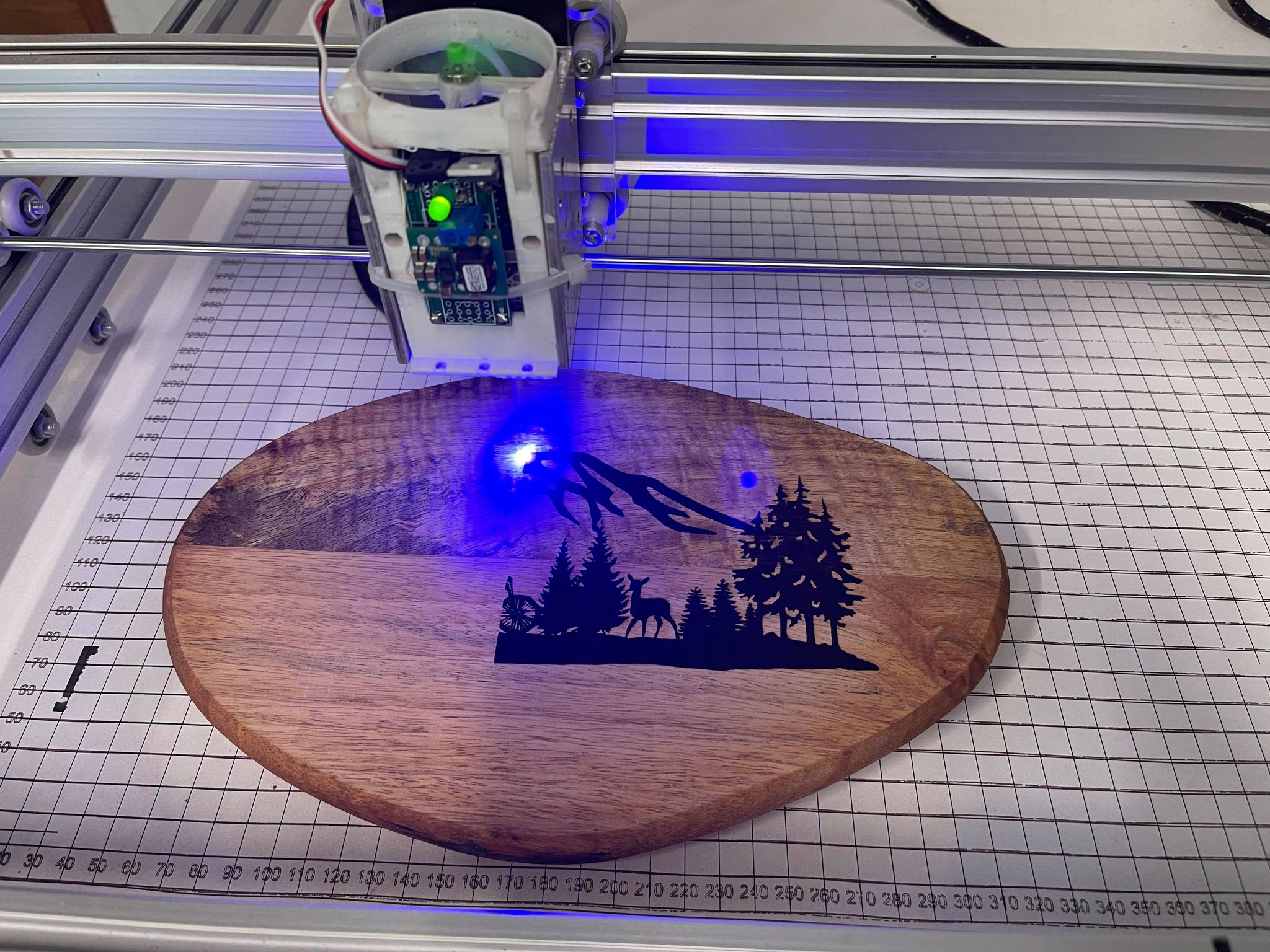 An L-Cheapo Mk7 Laser Cutter burning a pattern into a wood log